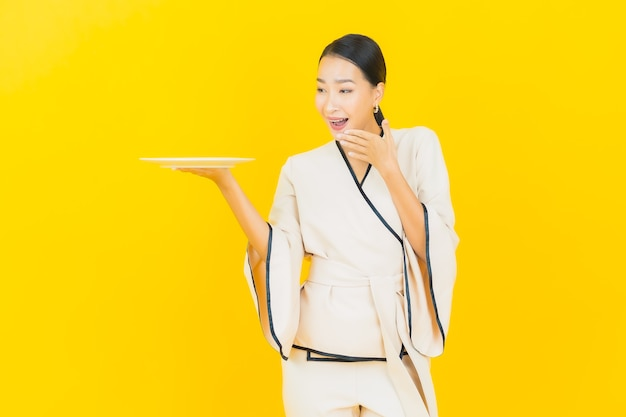 Portrait of beautiful young business asian woman with empty dish plate on yellow wall