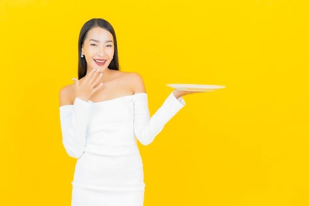 Ritratto di bella giovane donna asiatica di affari con il piatto vuoto del piatto sulla parete gialla