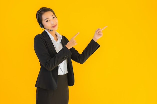 肖像画のヘッドフォンまたはヘッドセットと美しい若いビジネスアジア女性