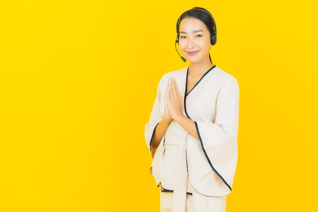 Portrait of beautiful young business asian woman with headset for call center customer care on yellow wall