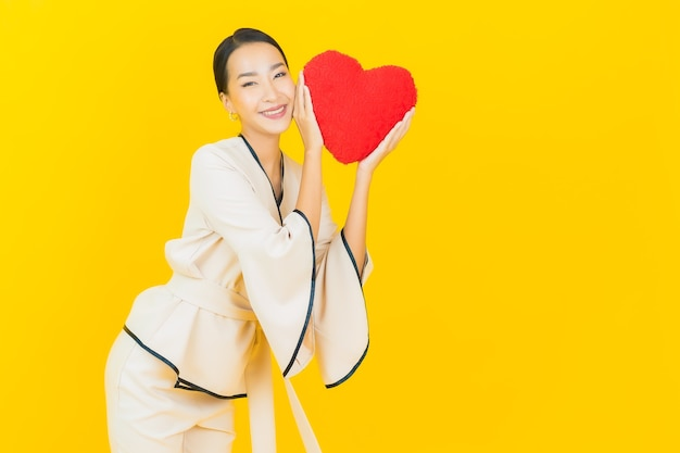 Portrait of beautiful young business asian woman with heart-shape pillow on yellow color wall