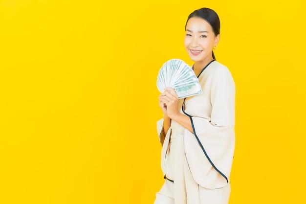 Ritratto di bella giovane donna asiatica di affari con un sacco di denaro contante e salvadanaio sulla parete gialla