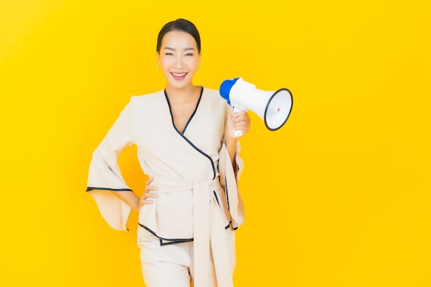 Portrait of beautiful young business asian woman with megaphone for communication on yellow wall