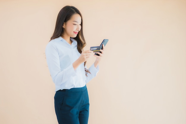 Женщина портрета красивого молодого дела азиатская с телефоном и кредитной картой