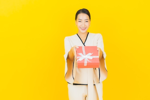 Ritratto di bella giovane donna asiatica di affari con il contenitore di regalo rosso sulla parete gialla
