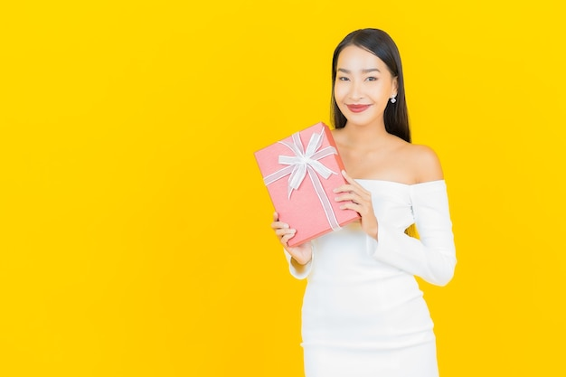 Portrait of beautiful young business asian woman with red gift box on yellow wall