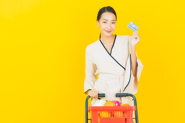 Portrait of beautiful young business asian woman with shopping basket grocery from supermarket on yellow wall