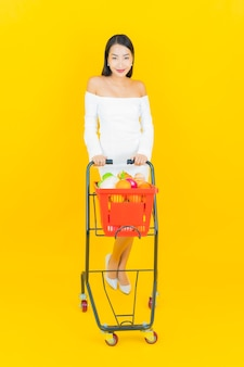 Portrait of beautiful young business asian woman with shopping basket with groceries from supermarket on yellow wall