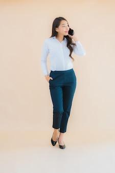 スマート携帯電話とコーヒーカップの美しい若いビジネスアジア女性の肖像画