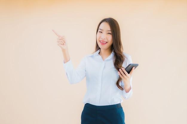 Женщина портрета красивого молодого дела азиатская с умным мобильным телефоном и кофейной чашкой