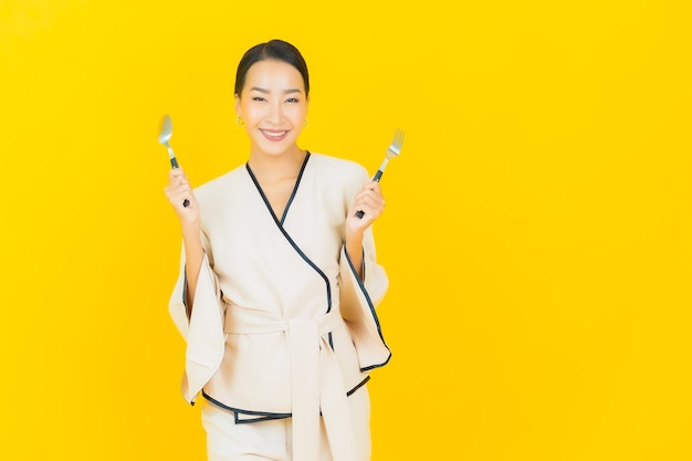 Portrait of beautiful young business asian woman with spoon and fork ready to eat food on yellow wall