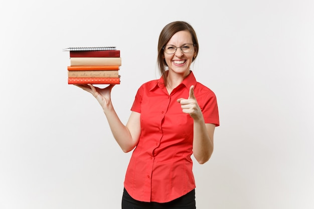 Portrait of beautiful young business teacher woman in red shirt, black skirt and glasses holding books in hands isolated on white background. education or teaching in high school university concept