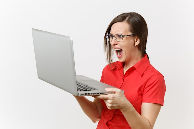 Portrait of beautiful young business teacher woman user in red shirt, glasses working typing on laptop pc computer isolated on white background. education or teaching in high school university concept