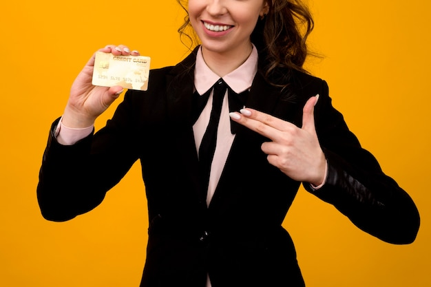 Portrait of a beautiful young business woman standing isolated over yellow background, holding credit card