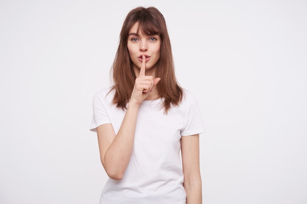 Portrait of beautiful young calm brown haired woman with natural makeup holding forefinger on her lips while standing over white wall, asking to keep secret