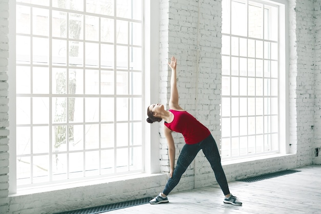 Portrait of beautiful young caucasian female in trendy sportswear working out in spacious light room by large windows, doing side bend exercise. yoga, fitness, sports and healthy lifestyle concept