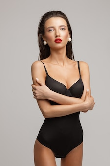 Portrait of beautiful young caucasian female with long dark hair, nice make up, red lips in black swimsuit mysterious looks to the camera