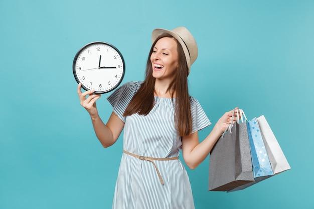 Портрет красивой молодой кавказской женщины в летнем платье, соломенной шляпе, держащей пакеты с покупками после покупок, круглые часы, изолированные на синем пастельном фоне. скопируйте место для рекламы.