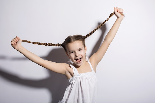 Portrait of a beautiful young caucasian woman in a light dress and pigtails smiling against a white background