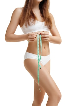 Portrait of beautiful young caucasian woman measuring her figure size with tape measure. woman's holding centimeter and measuring the size of thin body. image is not body shape retouched