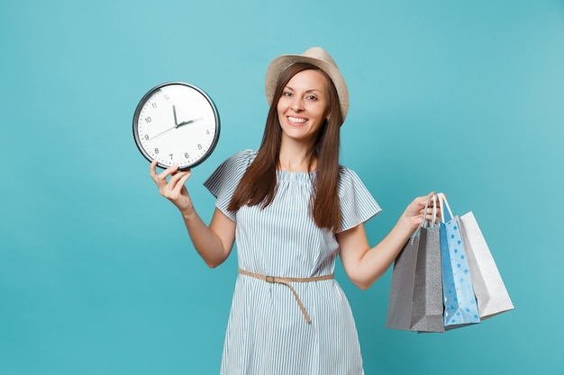 Portrait beautiful young caucasian woman in summer dress, straw hat holding packages bags with purchases after shopping, round clock isolated on blue pastel background. copy space for advertisement.