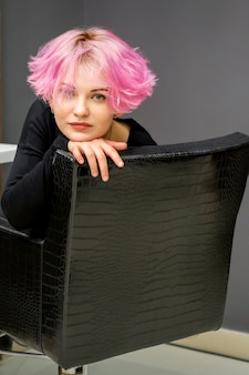 Portrait of a beautiful young caucasian woman with new short pink hairstyle sitting in a chair at a beauty salon