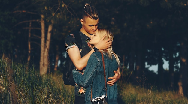 Portrait of a beautiful young couple embracing while woman is leaning hand on her boyfriend's chest with closed eyes against trees.