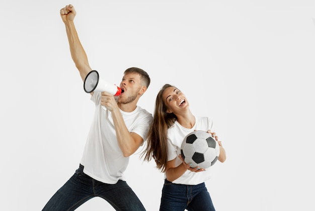Portrait of beautiful young couple football or soccer fans on white  space. facial expression, human emotions, advertising, sport concept