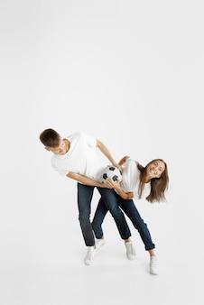 Ritratto di bella giovane coppia di tifosi di calcio o di calcio su sfondo bianco studio. espressione facciale, emozioni umane, pubblicità, concetto di sport. donna e uomo che salta, urla, si diverte.