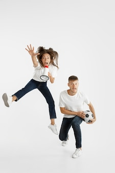 Portrait of beautiful young couple football or soccer fans on white wall. facial expression, human emotions, advertising, sport concept. woman and man jumping, screaming, having fun.