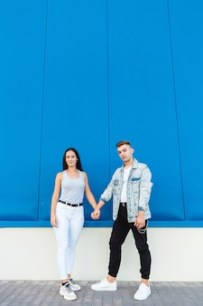 Portrait of a beautiful young couple in love holding hands with blue wall and copy space