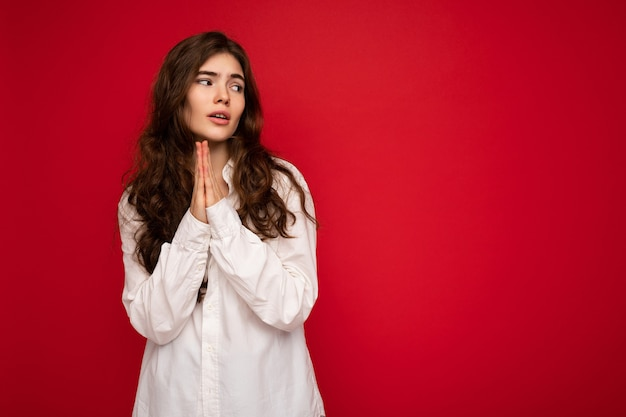 Portrait of beautiful young curly brunette woman wearing white shirt isolated on red background with