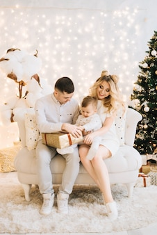Portrait of beautiful young family on christmas tree and white cotton. attractive parents and a little son open new year gifts