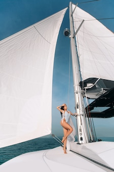 Portrait of beautiful young fashion woman standing and posing on sailboat or yacht in the sea wearing modern white swimsuit