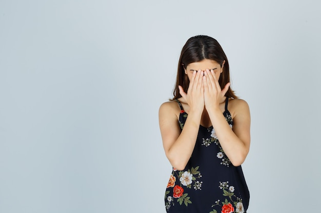 Portrait of beautiful young female covering face with hands in blouse