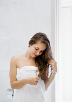 Portrait of beautiful young female model  in  bath applying hair oil. closeup of sexy woman in towel drying wet long hair. health and beauty concept. protection moisturizing cream.