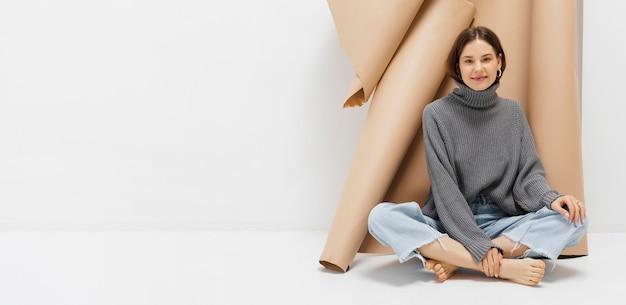 Портрет красивой молодой женщины, сидящей на полу