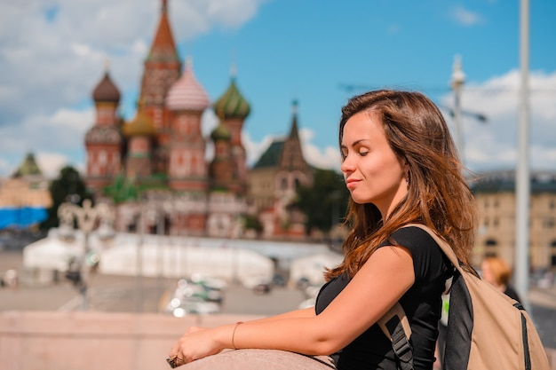 Portrait of a beautiful young female tourist with a view of the kremlin in moscow, russia