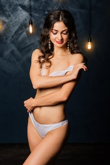 Portrait of a beautiful young female in a white underwear. morning of the bride.