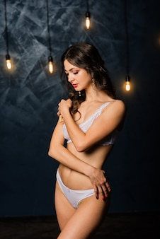 Portrait of a beautiful young female in a white underwear