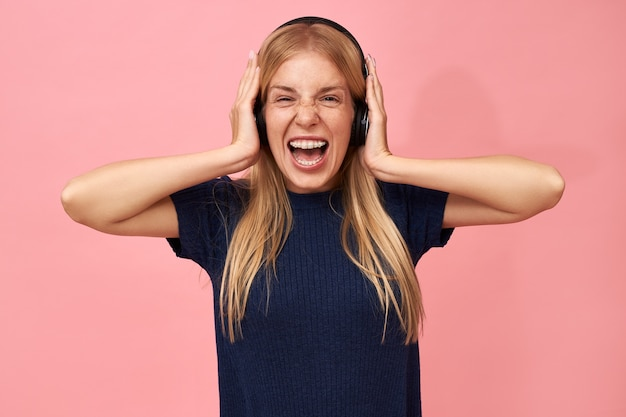 Portrait of beautiful young female with teeth brackets and blonde hair posing isolated in wireless headphones, screaming, listening to music via online streaming service