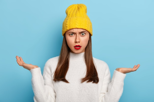 Portrait of beautiful young girl being questioned, spreads palms sideways, feels unawareness and doubt, wears red lipstick, wears yellow stylish hat, white jumper