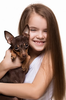 Portrait of a beautiful young girl caucasian snuggling with a cute terrier puppy dog