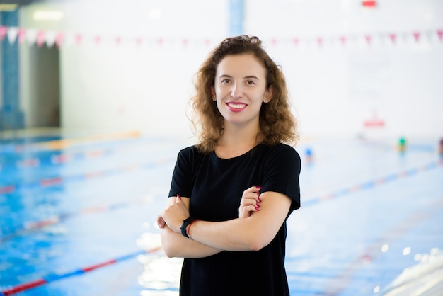 Portrait of a beautiful young girl coach near the swimming pool.