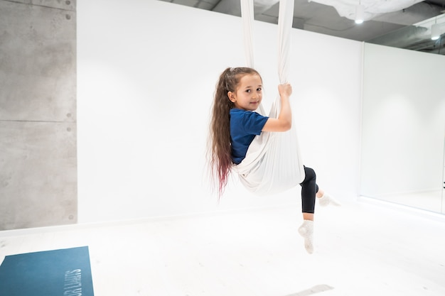 Portrait of a beautiful young girl engaged in fly yoga on canvases.