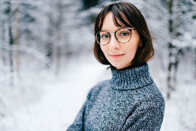 Portrait of beautiful young girl in glasses in snowy forest.