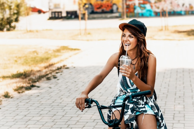 Portrait of a beautiful young girl in a hat with a bicycle on city