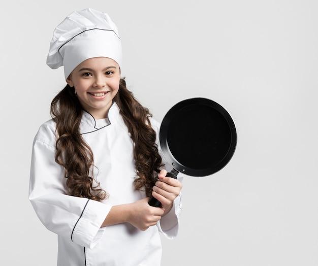 Ritratto di bella tenuta della ragazza che cucina pentola