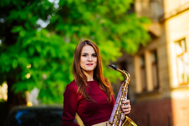 Portrait of a beautiful young girl walking on the street with a saxophone
