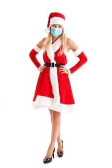 Portrait of a beautiful young girl wearing a christmas dress wearing a mask due to coronavirus pandemic